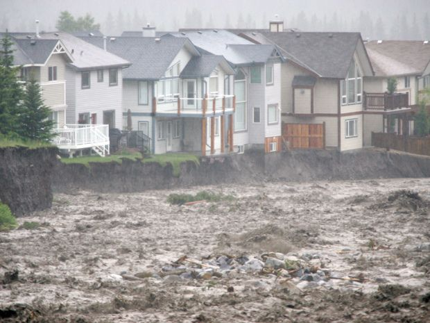 Debris and water pours across the Trans-Canada Highway as Canmore, Alberta struggles to deal with massive flooding Thursday morning (June 20, 2013).