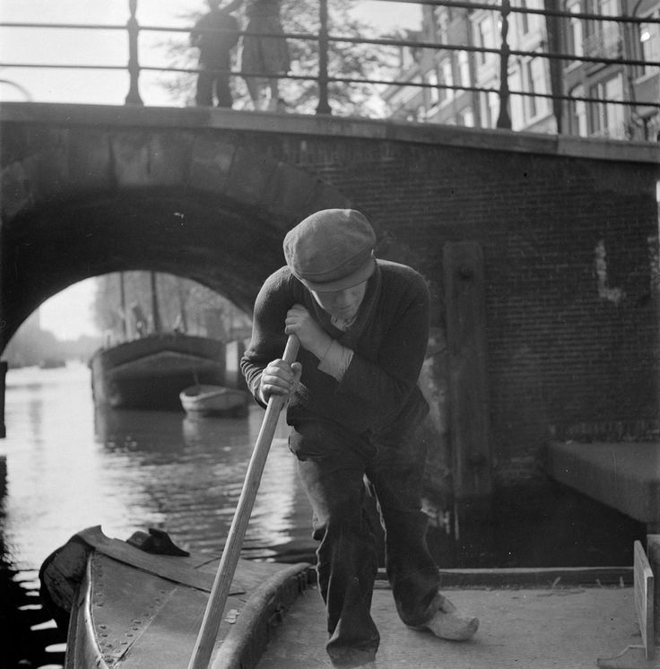 1950. Barge skipper pushes a barge through a canal in Amsterdam. Photo Dolf Kruger. #amsterdam #1950