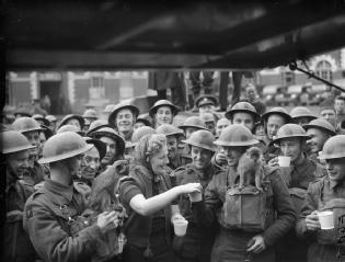 """BRITISH ARMY IN FRANCE 1940 """"WAR OFFICE SECOND WORLD WAR OFFICIAL COLLECTION"""" ByTaylor E A (Lt).Gracie Fields hands out tea to troops in a village near Valenciennes, one of whom has a pet monkey on his shoulder, 26 April 1940.L'ARMÉE BRITANNIQUE FRANCE 1940  partie de """"BUREAU DE GUERRE OFFICIEL COLLECTION LA DEUXIÈME GUERRE MONDIALE""""Par EA Taylor (Lt)  Gracie Fields mains sur le thé aux troupes dans un village près de Valenciennes, dont l'un a un singe sur son épaule, le 26 avril 1940."""