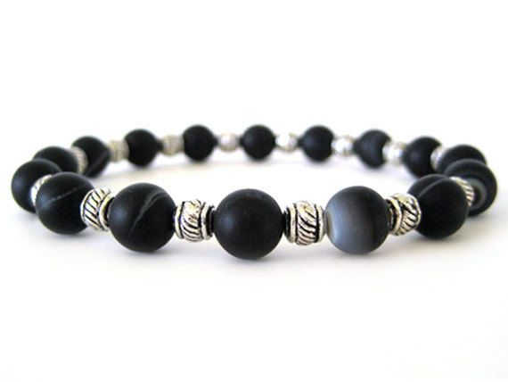 Masculine men's beaded stretch bracelet featuring 8mm matte black agate beads and pewter accent beads. The agate beads have very cool and subtle white and grey patterns swirling about adding to the uniqueness of this handmade bracelet. A great addition for the guy who loves to wear jewelry.