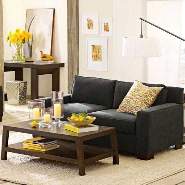 Темно-серый диван в интерьере современной гостиной, желтые акценты