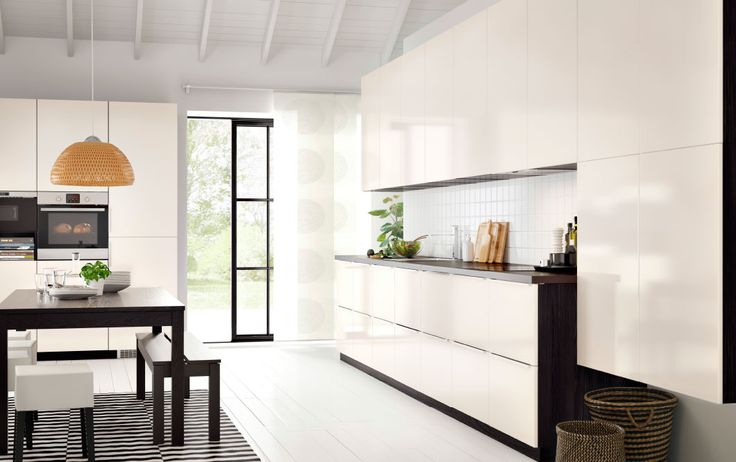 A contemporary kitchen with black brown cabinets, high gloss white cabinet doors and dark worktops