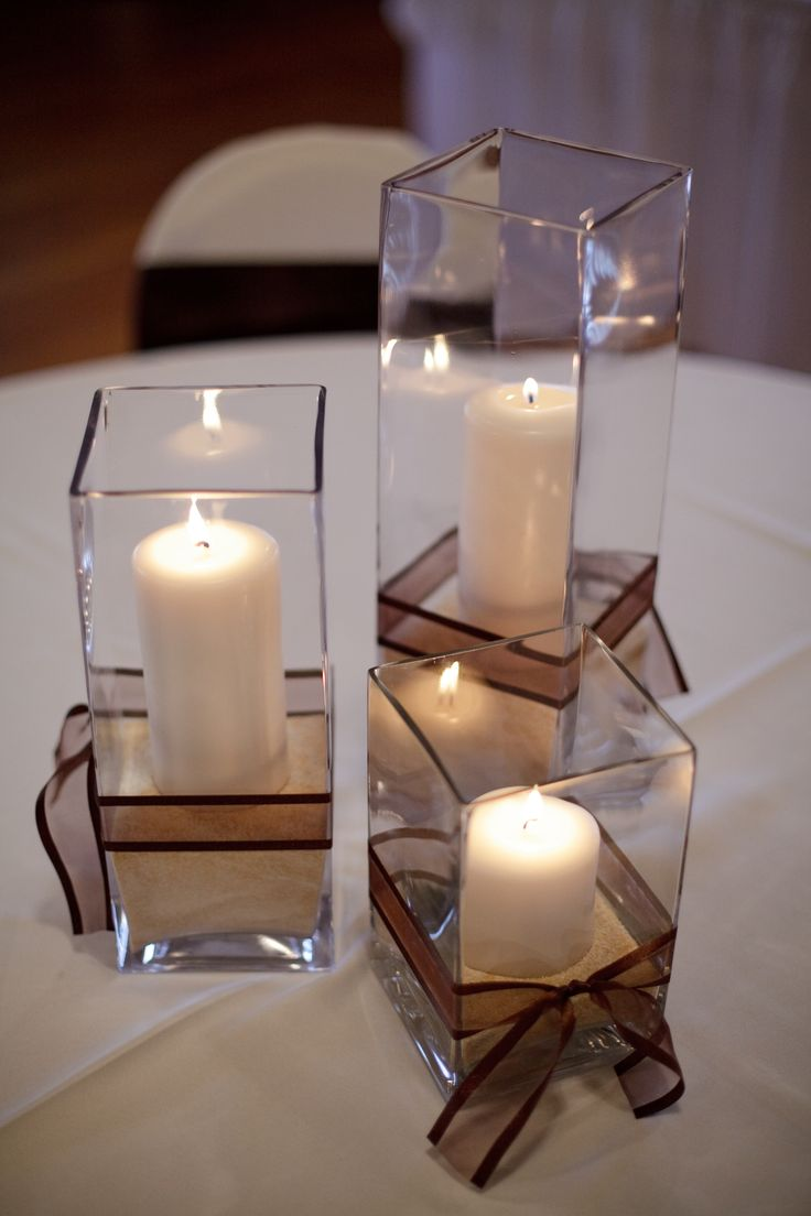 Simple centerpiece using sand, ribbon, and candles from Hobby Lobby with square vases rented from florist.