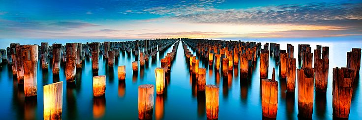 Wooden pillars are all that remains of Princes Pier, Port Melbourne, pending its redevelopment. The pier is a haven for recreational anglers, due to the abundant fish living around the pillars. Street lights illuminate the pillars at dusk, with the sunset fading into the south-west (right of image).