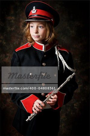 Foto de stock - portrait of a twelve year old girl wearing her marching band uniform holding her flute low-key studio shot                                                                                                                                                                                 Plus