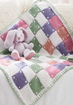 Knitted, but so cute! By juxtaposing different textures and introducing embroidered details, this baby blanket crosses the line between a knit and a 'quilt look'. Shown in Patons Beehive Baby Chunky.