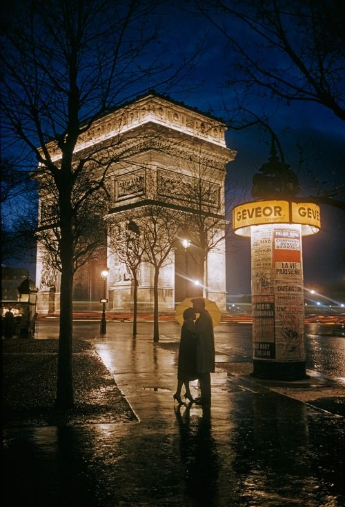 Young lovers embrace beside the Arc de Triomphe in Paris,...