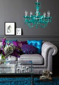 Cool chandelier, green, gray couch, green and purple pillows