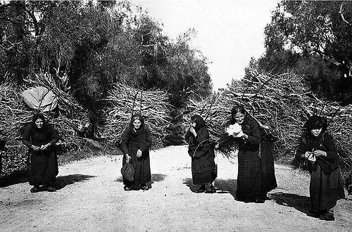 Γυναίκες της Πρέβεζας με βαρύ φορτίο από κλαριά. Ταυτόχρονα πλέκουν ή γνέθουν. 1912