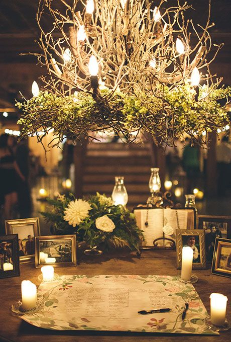Brides.com: . To really define the guestbook table at this wedding, Mint Springs Farm created a natural chandelier of greenery, branches, and faux candles.