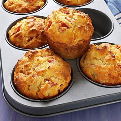A sütőt 200 fokra előmelegítjük. Egy 6 lyukú muffin formát papír kapszlival kibélelünk. (12 lyukú muffin sütőben is süthetjük, ez esetben kisebb muffinokat kapunk). A sütőporral elkevert lisztet és a cukrot egy nagy tálba tesszük. Hozzáadjuk a paradicsomot, az ananászt, a sonkát és a sajtot, majd összekeverjük. A két tojást a tejjel és az olajjal együtt felverjük, sózzuk, borsozzuk, majd a száraz hozzávalókhoz keverjük, addig, amíg össze nem áll.) A masszát a muffin formákba kanalazzuk (...