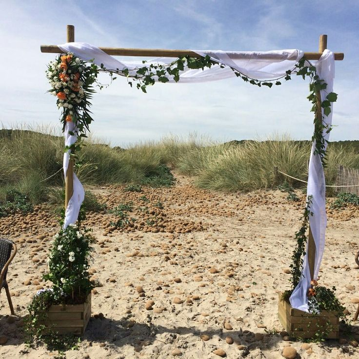 Beach wedding arch with flowering Jasmin, trailing ivy and roses and flowers to compliment the brides bouquet.