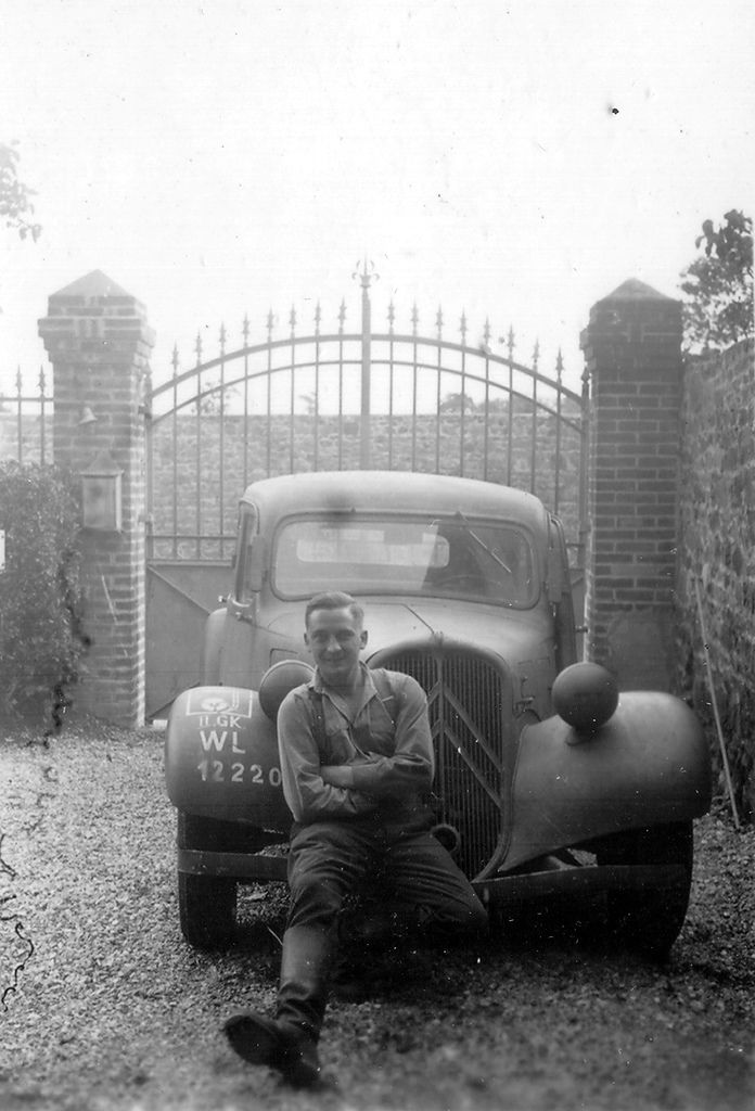 In a gravel driveway in front of a closed metal gate onto a brick wall, a front wheel drive Citroen BL 11cv, between the driver's door is ajar, the wiper blade on the passenger side is missing then the lights are hidden. Sue the front bumper, a German soldier in shirtsleeves sitting. Registration on the right front fender: GK-II Geräte Kolonne II WL Luftwaffe 12,220 Feldpostnummer the (postal code field) of the unit is Luftnachrichten-Regiment 13