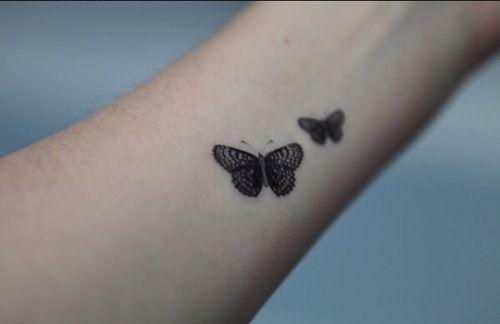 Pequeño tatuaje de dos mariposas en el antebrazo.