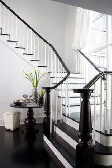 Dans la continuité du sol de l'entrée, les contremarches et la rampe en bois peintes en noir laqué en contraste avec le blanc de la cage d'escalier semblent attendre que la princesse apparaisse