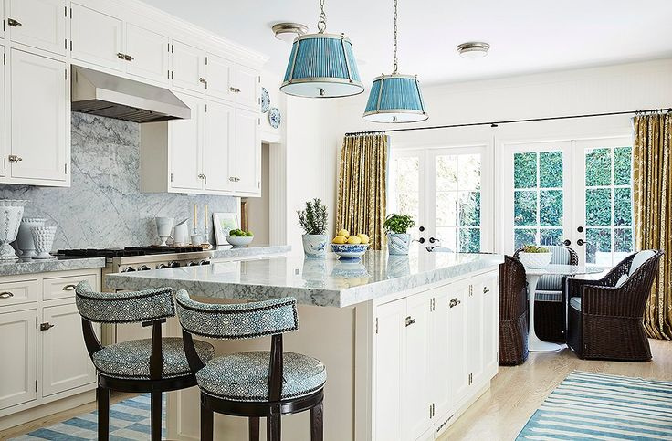 """The designer combined the original galley kitchen and adjoining maid's room to achieve an open, airy blue-and-white space that is another multifunctional area. """"We don't cook a lot, so it really serves as a family room,"""" says Mark. """"The TV is here, and we have lots of seating areas."""""""