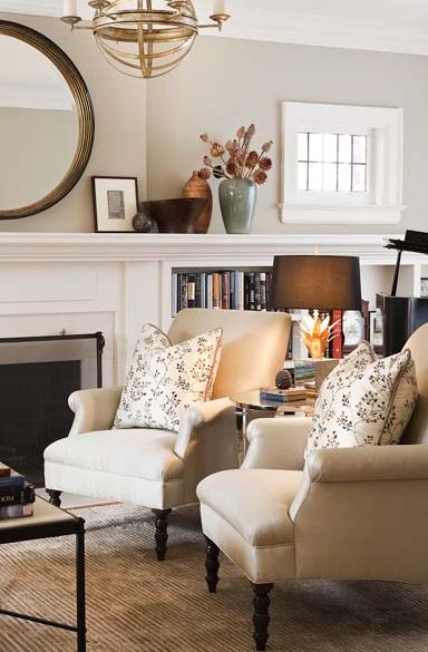 Jennifer Worts Design    transitional living room design with gorgeous rolled arm chairs with classic turned legs, floral pillows, fireplace, round black mirror, brass chandelier, built-ins bookshelves and soft gray paint wall color