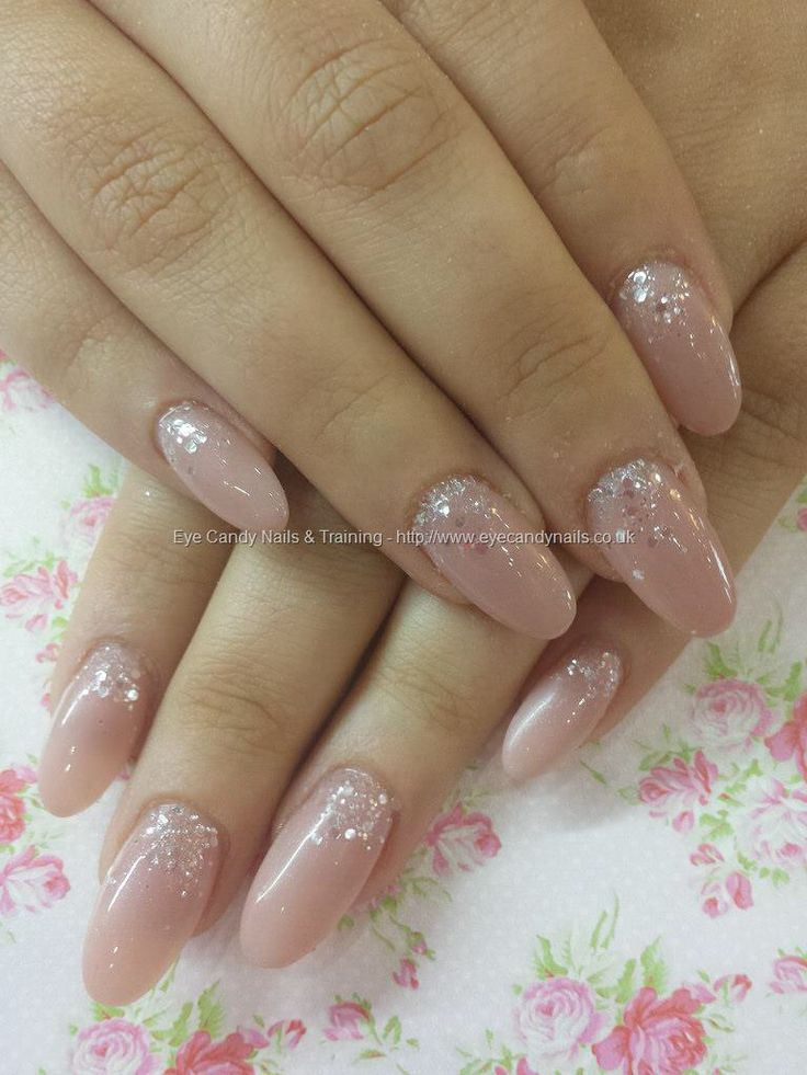 Nude acrylic nails with silver and diamonds.