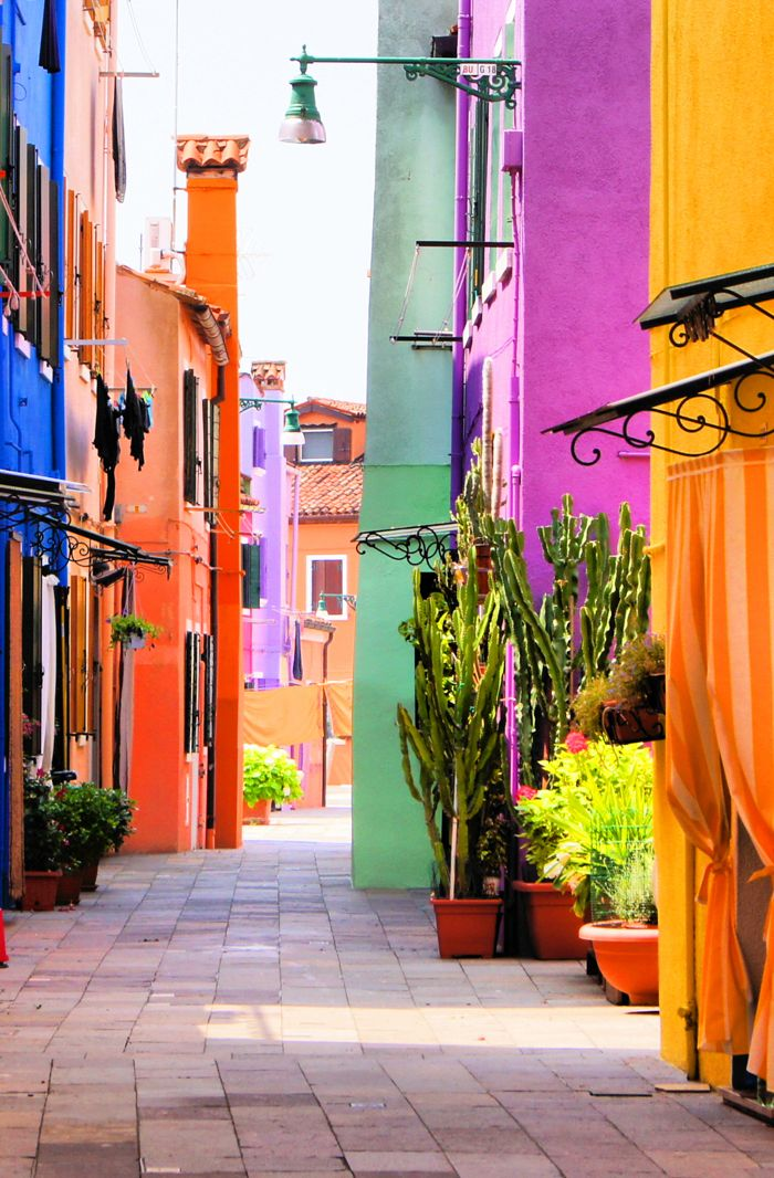 The island of Burano ~ in the Venetian lagoon, is made of picturque canals lined with brightly colored houses in Italy.