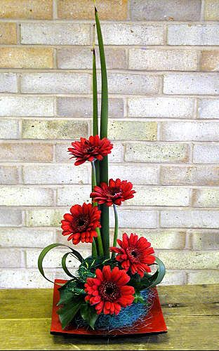 Red Gerberas Flower Arrangement - A red dish and red gerberas are the focal point of this exquisite red floral arrangement. - how to