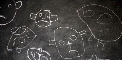 Dibujo de caras tristes en una pizarra