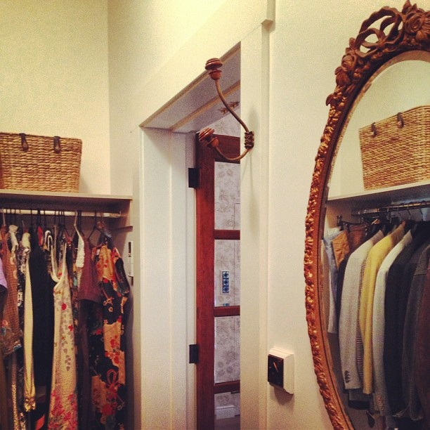walk in robe features reclaimed timber swing doors, restored 30 s mirror and antique french coat hooks.