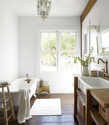 Style rétro dans cette salle de bain avec un meuble vasque et rangement en teck, baignoire et lavabo en céramique blanche agrémentés d'une robinetterie en laiton