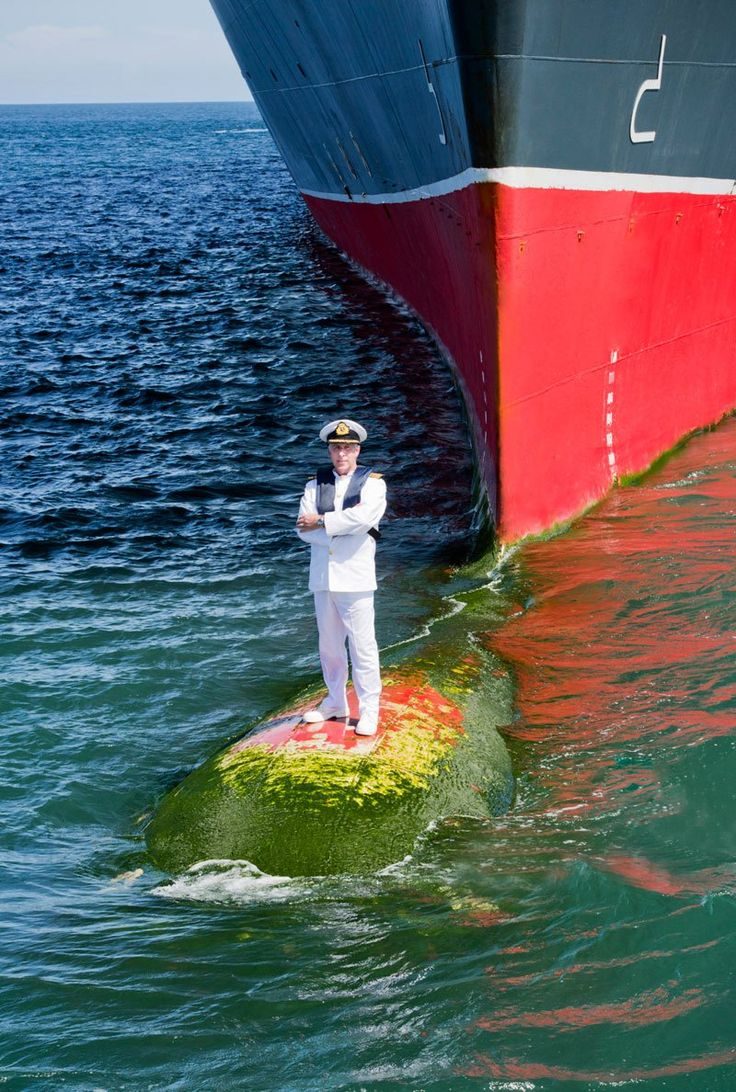 Captain Kevin Oprey, Master of Queen Mary 2, standing on the ship's bulbous bow (a protruding bulb at the front of a ship just below the waterline) a mile off the coast of Bali. Photographer James Morgan, 2014.