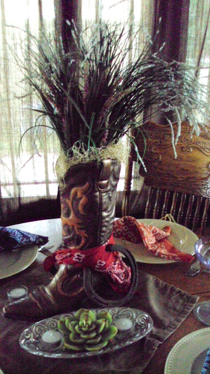 cowboy centerpiece with grasses  This is kind of what I meant with the boots, only reason I said baby boots (kids boots would work too) was space on table... leaning up on the mason jars or set just on big tables... depending on what we can find. - I don't want to use grasses, but what about a sheaf of wheat?