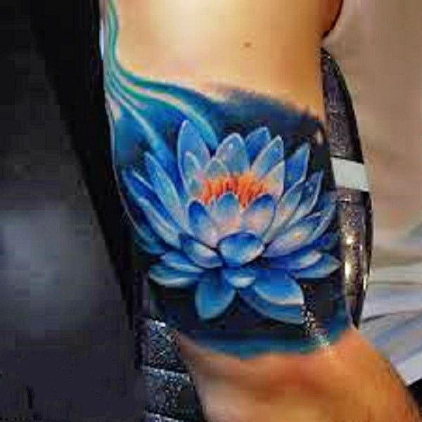 Magical looking blue lotus flower tattoo. The lotus flower is seen to be riding the current as it slides through the surface water in full bloom.