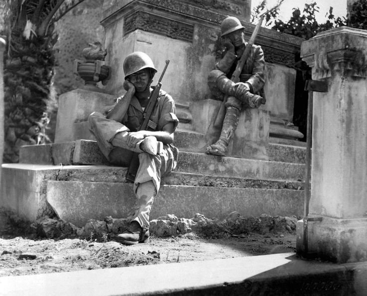 "Caption: ""U.S. Army Sgt. Norwood Dorman of ""E"" Company, 36th Field Artillery Regiment, from Benson, North Carolina, mimics the pose of a statue on a memorial for Italian soldiers of WWI while taking a brief rest during the Allied invasion of Sicily (Operation Husky). Brolo, Province of Messina, Sicily, Italy. 14 August 1943. Image taken by Robert J. Longini."""