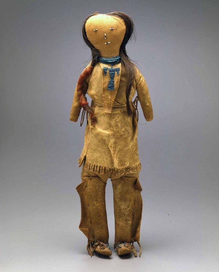"""Кукла, Южные Арапахо. Коллекция Warnock.  Период 1875-1900 - (1890). Кукла мужчины одета в рубашку из оленьей кожи. На передней части рубахи вышит бисером образ """"Птицы Грома"""". Нк кукле кожанные леггинсы и мокасины с вышивкой бисером и бахромой. Ткань для тела,  глаза, нос и рот из бисера. Высота: 36.8 см. Источники: Alexander GalleryEpic Fine Arts Co./Masco Corp. Splendid Heritage."""