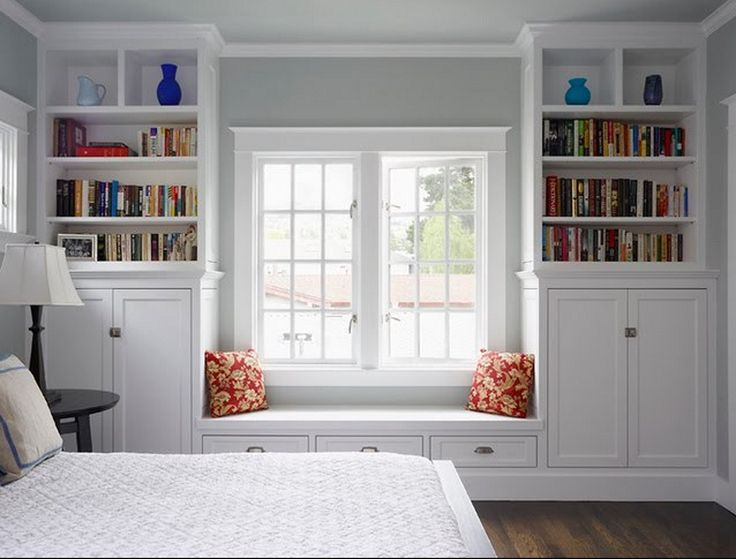 Built-in shelves, cabinets, drawers and window seat in large bedroom