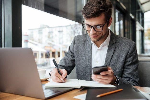 Baixe Empresário Sorridente Em óculos, Sentado Junto à Mesa No Café Com O Computador Portátil Enquanto Estiver Usando O Smartphone E Escrevendo Algo gratuitamen…   Retrato de homens, Empresário, Retrato corporativo