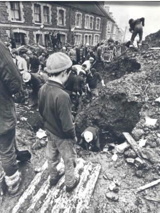 A young boy looks on as rescuers dig for survivors.The school was in session; it being the last day before half term week. 144 children and adults died – 116 were schoolchildren. Half of all the children at Pantglas Junior School were killed together with 5 of their teachers.