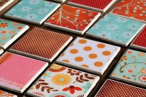 Coasters made of tiles, scrapbook paper, mod podge, spray paint, and felt pads.