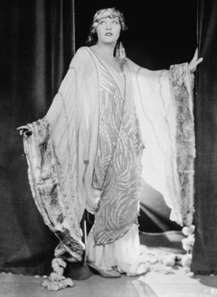 American film star Gloria Swanson looking incredibly dramatic in a sweeping, fur-trimmed robe, c.1920s.