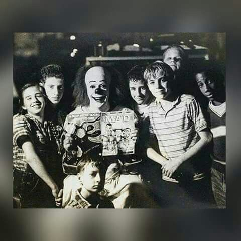 "Tim Curry's Pennywise the Clown with the young cast of actors from Stephen King's movie ""It."""