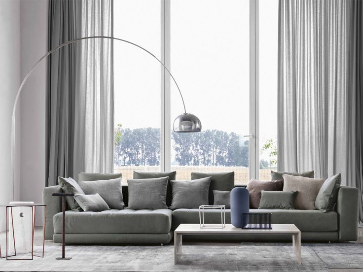 This sunlit living room features the FLOS Arco floor lamp, floor to ceiling windows and gray carpeting.