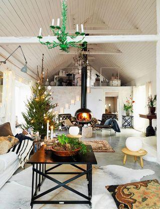 """JUL MED NATURLIG CHARM: I år är det naturlig jul som gäller. Det blir naturfärger som grönt, brunt och mycket trä. Med temat """"naturligt"""" blir det förstås också mycket naturgodis som nötter och äpplen. Mycket av rekvisitan kommer från den egna tomten och skogen. [...]På betonggolvet ligger en kohud från Ikea och en äkta matta fyndad på Myrorna. Det svarta soffbordet är från Day och det stora fatet ovanpå kommer från Indiska. Handöl-kamin och Karin-fåtöljer köpta på Blocket. Furupallar Ikea PS…"""