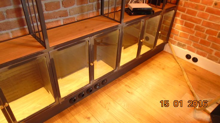 Living room metal library. Raw metal with mat transparent varnish. Beveled glass at the bottom. Oiled oak shelves. Enjoy the classic design with a hint of industrial look. Design and realization by Zbigniew Bakanowicz Private apartment Warsaw - Poland