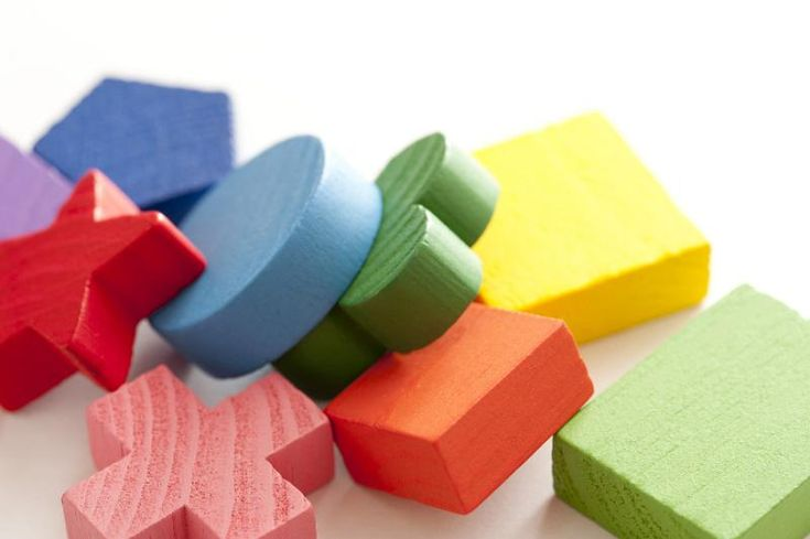 Colorful educational wooden toy blocks in a variety of different basic geometrical shapes lying in a heap on white - free stock photo from www.freeimages.co.uk