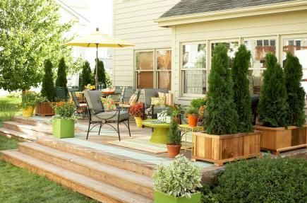 Three wide steps transition from the yard to a wide deck featuring an area for conversation and one for dining.