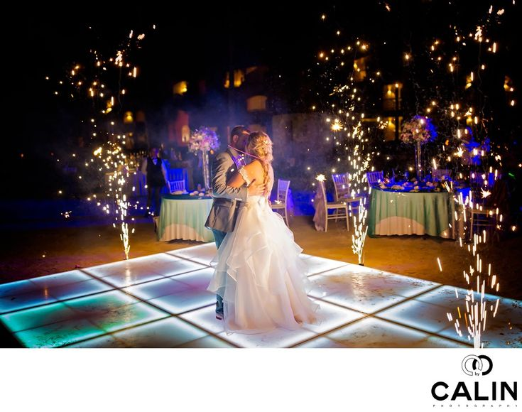 Photography by Calin - Barcelo Maya Palace Deluxe Wedding - First Dance:  This is a photo of the first dance at a Barcelo Maya Palace Deluxe wedding. In this wedding picture, the bride and groom are dancing on a lit dance floor surrounded by fireworks. In the background, we can see the guests watching the bride and groom's first dance.  One of the options a couple can buy when booking a Barcelo Maya wedding, is the fireworks during the first dance. Despite the fact the fireworks cost about…