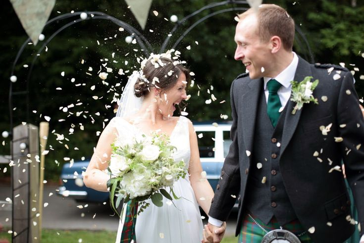 Bride & Groom Confetti Exit - Image by Dasha Caffrey - Rustic Wedding With Tartan Accents And Bride In Elegant Gown From Go Bridal With A Sassi Holford Veil And Rachel Simpson Shoes With Groom And Groomsmen In Kilts