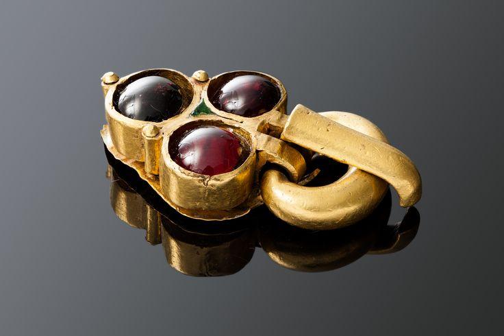 Пряжка с овальной рамкой и треугольным щитком. Золото, гранаты. 5,9х3,2х1,3 см. V в.