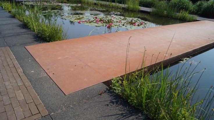 Grote vijver met brug van Cortenstaal platen. Te zien in De Tuinen van Appeltern.