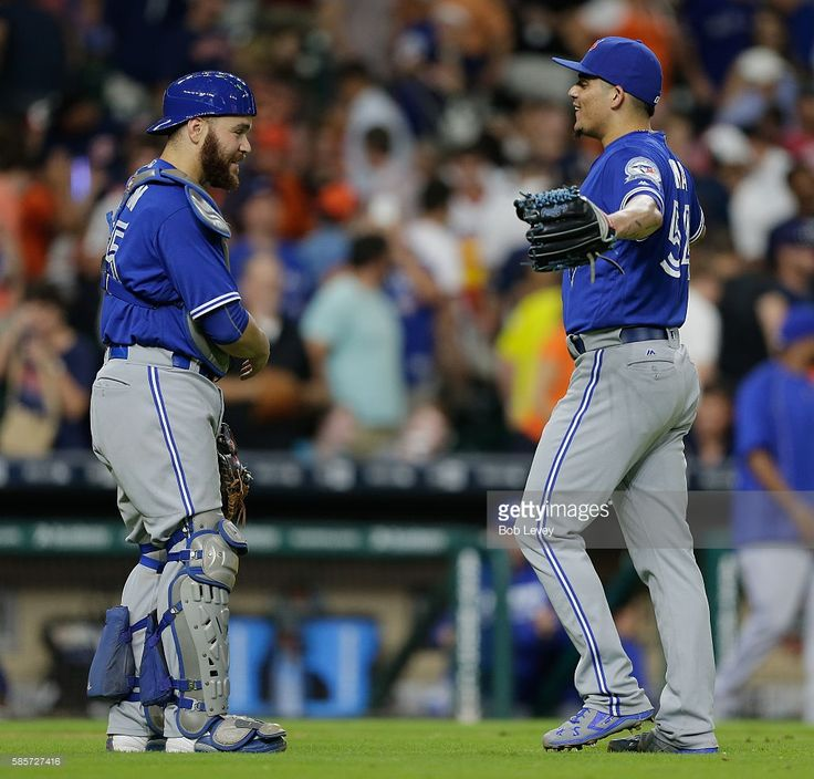 Roberto Osuna #54 of the Toronto Blue Jays hugs catcher Russell Martin after the…