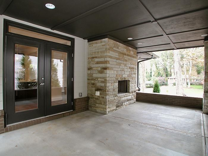 A covered porch of a Modern Prairie style home. The kitchen opens to the porch via glass doors and the patio wraps around to the backyard and family room. The porch features a stacked stone fireplace with gas starter. The columns of the porch are stacked stone and the porch walls are brick.