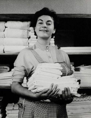 Trotse huisvrouw voor linnenkast met stapels gewassen en gestreken was.